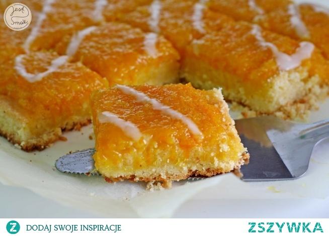 Mazurek pomarańczowy    Ciasto:      600 g mąki krupczatki     250 g cukru pudru     350 g masła     3 żółtka (u mnie 4)      szczypta soli   Masa:      4 pomarańcze     1 cytryna     250 g cukru*   * jeśli wolicie słodsze masy dodajcie 300 g cukru  Przygotowanie:  Mąkę wymieszać z cukrem pudrem, posiekanym masłem, żółtkami (jeżeli po dodaniu 3 żółtek ciasto nie będzie chciało Wam się zagnieść dodajcie jeszcze jedno) i solą. Zagnieść kruche ciasto, owinąć w folię spożywczą i wstawić na 1 godzinę do lodówki. Wyjąć, rozwałkować na gruby placek, ułożyć na blasze (o wymiarach ok. 35x25 cm) wyłożonej papierem do pieczenia, formując rant (niekoniecznie) i gęsto ponakłuwać widelcem. Piec w piekarniku nagrzanym do 200 stopni przez 15-10 minut, do uzyskania złotego koloru.   Pomarańcze i cytryny wyszorować w gorącej wodzie. Skórkę zetrzeć (bez białej, gorzkiej warstwy), a miąższ zmiksować. Skórkę, miąższ i cukier podgrzewać w rondlu przez ok. 30 minut, często mieszając. Kiedy masa zgęstnieje, ciepłą wylać na upieczony spód mazurka (masa powinna być na tyle gęsta, że nie ścieka nawet na spodzie bez rantu) i odstawić do zastygnięcia. Udekorować kandyzowaną pomarańczą, lukrem lub migdałami.