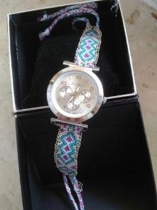 Prześliczny zegarek ALDO z ręcznie robionym paskiem z muliny w kolorach błękitu, fioletu i beżu. Idealnie prezentuje się do eleganckiej stylizacji jak i na co dzień, a zapięcie ...
