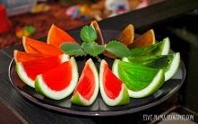 Miąższ z owoców wykrawamy i napełniamy go płynną galaretką. Potem owoce kroim...
