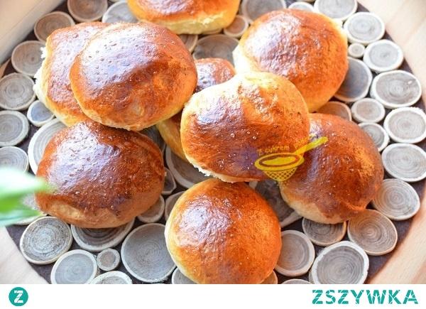 """bułeczki maślane (puszyste)   0,5 kg mąki pszennej tortowej + ewentualnie 2 łyżki do podsypania 3 żółtka (z jajek M) 50 gramów stopionego, schłodzonego masła 4 kopiaste łyżki cukru 2 łyżki cukru z wanilią 50 gramów drożdży 1 szklanka mleka w temp. ciała szczypta soli  do posmarowania: 1 rozkłócone jajo + 2 łyżki zimnego mleka   Drożdże rozprowadzić w mleku dodając 1 łyżkę cukru i 2 łyżki mąki, odstawić w ciepłe miejsce do """"ruszenia"""".  Mąkę przesiać z solą, resztą cukru, cukrem waniliowym, wlać rozczyn, dodać żółtka (masła jeszcze nie dodawać),krótko zagnieść lepkie ciasto, wlać masło, wgnieść je w ciasto. Ciasto wsadzić do omączonej michy, odstawić do podwojenia objętości.  Po tym czasie krótko zagnieść, utoczyć wałek, podzielić go na 10 - 12 części, z każdej uformować bułeczkę, układać je na blasze wyłożonej papierem do pieczenia w odstępach około 5 - 6 cm, odstawić na 30 minut do podrośnięcia.  Po tym czasie każdą z bułeczek spłaszczyć lekko z góry dłonią, posmarować jajem z mlekiem. Piekarnik nagrzać do 180 stopni, włożyć bułeczki, piec około 22 - 25 minut (funkcja grzania góra - dół, bez termoobiegu, na środkowym poziomie).  UWAGA: Jeśli zauważymy, że bułeczki za bardzo się przypiekają z góry przykryjmy je folią aluminiową i spokojnie pieczmy dalej."""
