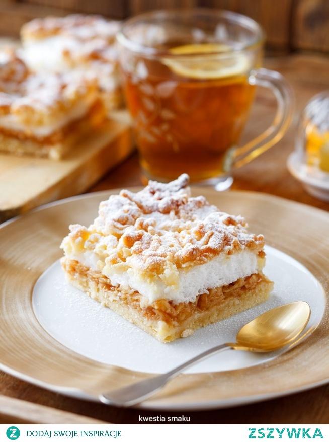 Szarlotka z bezą  Ciasto kruche      3 szklanki (450 g) mąki pszennej     1/3 szklanki cukru     1 cukier wanilinowy     1 łyżeczka proszku do pieczenia     250 g masła      50 g smalcu lub masła     5 żółtek  Jabłka      1 kg jabłek odmiany szara reneta     1 cukier wanilinowy     sok z 1/2 cytryny     1 budyń śmietankowy lub waniliowy     1 łyżeczka cynamonu  Beza      5 białek     1 i 1/2 szklanki cukru     2 łyżki mąki ziemniaczanej     cukier puder do posypania  Dodaj notatkę Przygotowanie Ciasto kruche      Do miski lub na stolnicę przesiać mąkę, dodać cukier, cukier wanilinowy i proszek do pieczenia. Dodać starte na tarce lub drobno posiekane masło oraz posiekany smalec. Ucierać składniki palcami lub siekać składniki na stolnicy aż powstanie drobna kruszonka.     Dodać żółtka i zagnieść ciasto łącząc ze sobą wszystkie składniki. Uformować kulę, rozpłaszczyć ją, zawinąć w folię i schować do lodówki na ok. pół godziny.  Jabłka      Jabłka obrać ze skórki i zetrzeć na tarce o grubych oczkach. Dodać sok z cytryny, proszek budyniowy oraz cynamon, wymieszać, odstawić. Piekarnik nagrzać do 175 stopni C.     Wyjąć ciasto z lodówki, odłożyć 1/3 ciasta i schować je z powrotem do lodówki. Z 2/3 pozostałego ciasta uformować kulę i pokroić ją na cienkie plastry, układać je na dnie blaszki o wymiarach 25 x 35 cm posmarowanej masłem i wyłożonej papierem do pieczenia lub posypanej mąką. Plastry ugnieść palcami na jedną równą warstwę i wstawić do piekarnika na 10 minut.  Beza      Ubić białka na sztywną pianę ze szczyptą soli, następnie stopniowo dodawać cukier cały czas ubijając. Po skończonym cukrze ubijać jeszcze przez ok. 2 - 3 minuty. Dodać mąkę ziemniaczaną i zmiksować.     Na podpieczony spód wyłożyć jabłka, na wierzchu bezę i na końcu starte na tarce ciasto z lodówki. Piec przez ok. 35 minut na złoty kolor, oprószyć cukrem pudrem.  Wskazówki  Zwróćmy uwagę na wielkość blaszki, jej powierzchnia nie może być mniejsza niż podana w przepisie.