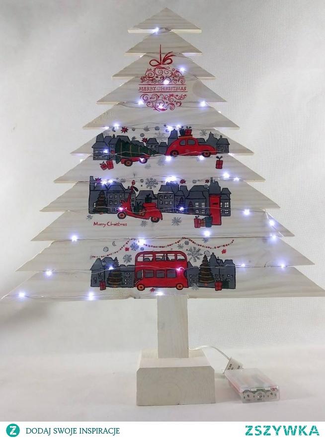 Drewniana choinka w kolorze białym z malowanym motywem. Choinka z deski sosnowej pomalowana białą bejcą dodatkowo zabezpieczona bezbarwną farbą akrylową. Światełka LED (50) na metalowym druciku na baterie. Choinka wysokości ok. 64 cm, szerokości u podstawy ok.48 cm. Na choince namalowane trzy motywy świątecznego miasteczka z czerwonym autami i autobusem, farbami akrylowymi. Bardzo ciekawa, prosta ozdoba świąteczna, która umili czas Świąt nie tylko w domu ale też w biurze. Może służyć przez wiele lat. W ofercie inne wzory choinek. Jedyny egzemplarz.  Zapraszam :)