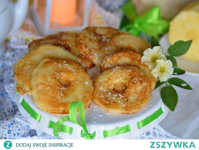 Ananasy w cieście      mąka pszenna     170 gramów     mleko     140 mililitrów     jajka     2 sztuki     cukier puder     2 łyżki     cukier wanilinowy     1 łyżeczka     wiórki kokosowe     4 łyżki     proszek do pieczenia     0.5 łyżeczki     sól     1 szczypta     ananas świeży     1 sztuka     olej kokosowy     6 łyżek     cukier puder do posypania     2 szczypta  Ananasa obrać ze skóry, pokroić na plastry około 5-8mm, a z każdego plastra wykroić twardy środek (rdzeń).  Mleko zmiksować z jajkami, szczyptą soli, wiórkami i cukrami. Następnie dodać mąkę wymieszaną z proszkiem do pieczenia i całość dokładnie wymieszać.   Na patelni rozgrzać niewielką ilość oleju kokosowego, plastry ananasa obtoczyć w cieście i smażyć na złoty kolor z obydwu stron. Gotowe ananasy w cieście posypać cukrem pudrem.