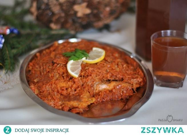 Ryba po grecku      500 g filetów z dorsza lub innej ryby     5 marchewek     2 pietruszki     kawałek selera     2 cebule     2-3 listki laurowe     5 ziarenek ziela angielskiego     5 ziarenek pieprzu     150-200 g koncentratu pomidorowego     sól, pieprz     cukier do smaku     1-2 łyżeczki musztardy     ok. 300 ml wody  Dodatkowo:      olej do smażenia warzy     olej do smażenia ryby     mąka, jajko i bułka do panierowania filetów  Filety rozmrozić, osuszyć, pokroić na mniejsze kawałki, obtoczyć w mące, jajku i bułce. Smażyć na rozgrzanym oleju na złoty kolor. Odłożyć na talerz wyłożony ręcznikiem papierowym, by pozbyć się nadmiaru tłuszczu.  Marchewki, pietruszki i selera obrać. Zetrzeć na grubych oczkach tarki. Cebulę pokroić w piórka. Warzywa podsmażyć w garnku lub na dużej patelni na niewielkiej ilości oleju, a następnie zalać je wodą, dodać przyprawy i dusić do miękkości. Następnie do warzyw dodać koncentrat i musztardę, wymieszać i gotować jeszcze przez kilka minut na małym ogniu.  Usmażoną rybę ułożyć na półmisku i przykryć ją warzywną kołderką.  Można podawać zarówno na ciepło, jak i na zimno.