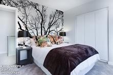 Nietuzinkowa fototapeta czarno biała nad zagłówkiem łóżka, z motywem gałęzi d...