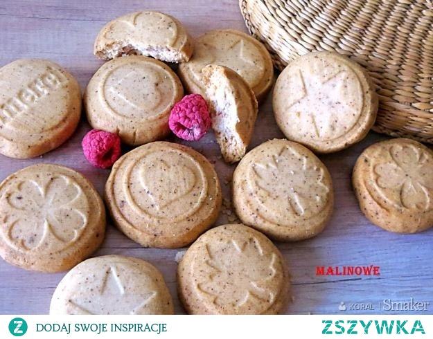 Malinowe ciastka       mąka pszenna 300 g     budyń malinowy ( bez cukru) 80 g     masło lub margaryna 120 g     cukier puder 60 g     maliny liofilizowane ok.5-8 g  Wychodzi około 28 ciastek. Mąkę mieszamy z budyniem i cukier puder, dodajemy pokrojone schłodzone masło i maliny. Można dodać kilka kropli aromatu. Wszystko miksujemy w robocie do uzyskania jednolitej masy. Z gotowego ciasta odrywamy kawałki wielkości małego orzecha włoskiego, lub jeszcze mniejsze. Z kawałków forujemy kulki, przekładamy je na blachę z papierem do pieczenia. Za pomocą stempli lub foremek lekko spłaszczamy nadając wzorek. Pieczemy około 20 minut w 180 C.
