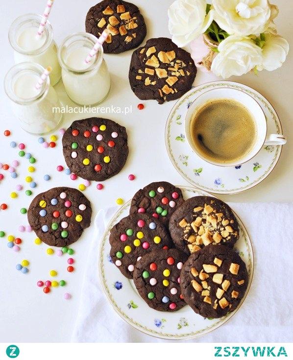 Proste MEGA CZEKOLADOWE ciastka Składniki na około 15 ciastek, składniki powinny być w temperaturze pokojowej: 150g miękkiego masła (w temperaturze pokojowej) 150g ciemnego trzcinowego cukru dark muscovado (możemy zastąpić jasnym brązowym) 1 jajko 150g mąki pszennej (użyłam tortowej) 7 łyżek kakao bez cukru (około 70g) 1/2 łyżeczki sody szczypta soli 100g posiekanej gorzkiej czekolady 100g posiekanej mlecznej czekolady 2-3 krople aromatu śmietankowego lub waniliowego (niekoniecznie) Dodatkowo: około 100g grubo posiekanej białej czekolady lub kolorowych cukierków typu lentilki 1. Masło utrzeć z cukrem, ucierać mikserem ustawionym na najwyższe obroty przez około 2-3 minuty. Następnie dodać jajko i wymieszać mikserem do połączenia składników. 2. Do maślanej masy dodać mąkę, kakao, sodę, sól, aromat i wymieszać mikserem na niskich obrotach, aż powstaną okruchy (patrz FILM). Odstawić mikser, dodać mleczną oraz gorzką czekoladę i rękoma zagnieść ciasto. Ciasto zawinąć w folię spożywczą i odstawić w chłodne miejsce na około 30 minut. 3. Ze schłodzonego ciasta formować w rękach kulki i układać je na blaszce wyłożonej papierem do pieczenia lub matą silikonową, ciasteczka spłaszczać. Proszę zachować między ciasteczkami odstępy ponieważ rosną podczas pieczenia. W wierzch ciastek powciskać posiekaną białą czekoladę lub kolorowe cukierki. 4. Ciasteczka wstawić do nagrzanego piekarnika, piec w temperaturze 170C na funkcji termoobieg przez około 13-15 minut. Po wyjęciu z piekarnika proste, MEGA CZEKOLADOWE ciastka odstawić co przestygnięcia. Udanych wypieków :)