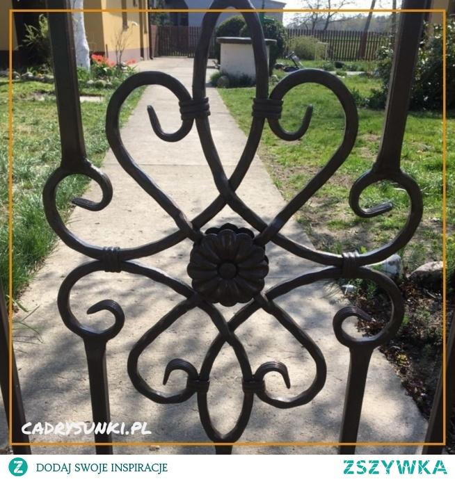 Elementy kowalstwa artystycznego zastosowane w bramie ogrodowej.