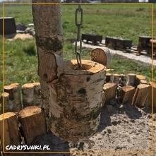 Drewniana dokoracja ogrodu przypominająca studnię na wodę.