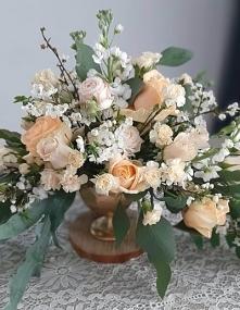 Brzoskwiniowy bukiet kwiatów w złotym pucharku.