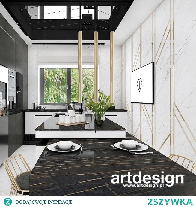 Inspiracja w projektowaniu kuchni: dekoracyjna ściana ze spieku z kompozycją z listw w złotym kolorze, wysoka zabudowa meblowa i duża wyspa z miejscem do spożywania posiłków. Elegancko i wygodnie :)