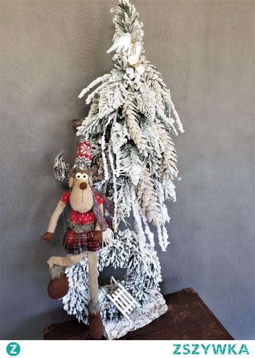 Ośnieżona biała choinka z wiankiem i świątecznym reniferem
