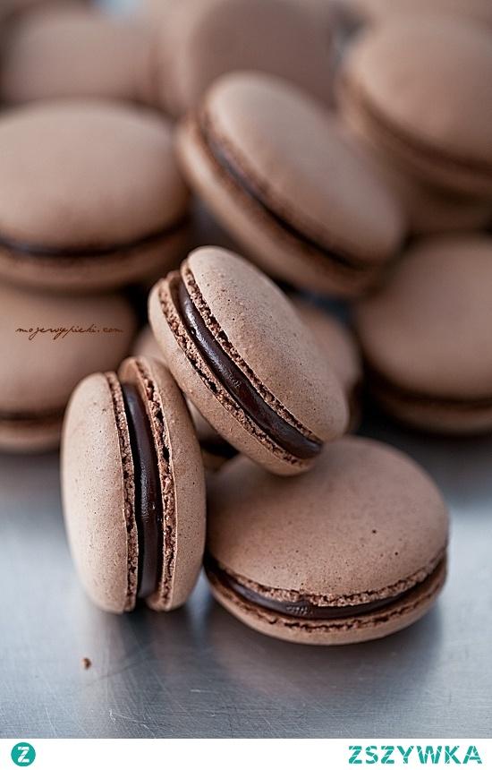 Składniki na około 30 ciastek (lub około 40 mini - makaroników): 150 g zmielonych migdałów 115 g cukru pudru 35 g kakao 120 g białek (podzielone na 60 g + 60 g), w temperaturze pokojowej 185 g cukru (podzielone na 150 g + 35 g) 50 ml wody Migdały, cukier puder i kakao umieścić w malakserze. Zmiksować do połączenia, przez około 2 minuty. Przesiać przez bardzo drobne sitko do większego naczynia usuwając wszelkie większe kawałki migdałów (w to miejsce dosypać nowych, drobniejszych, zazwyczaj jest to około 1 łyżeczki). Dodać 60 g białek, dokładnie wymieszać. W misie miksera umieścić dodatkowe 60 g białek (misa powinna być sucha, bez śladów tłuszczu, białka idealnie oddzielone od żółtek). Obok w małym kubeczku przygotować 35 g cukru. W małym garnuszku umieścić 150 g cukru i 50 ml wody. Wymieszać, zagotować. W garnuszku umieścić termometr cukierniczy i gotować na średniej mocy palnika (ważne: nie mieszając ani razu!) do osiągnięcia na nim temperatury 118ºC (245ºF). W międzyczasie, gdy syrop dochodzi do temperatury 100ºC (210ºF) zacząć ubijać białka. Białka ubijać jak na bezy - do sztywności, pod koniec miksowania dosypując cukier, łyżeczka po łyżeczce, cały czas miksując. Gdy syrop osiągnie wymaganą temperaturę natychmiast ściągnąć go z palnika i powoli, cienką strużką wlewać syrop cukrowy do ubijanych białek (ubijamy na razie na małych obrotach - tylko podczas wlewania syropu cukrowego, by nie znalazł się na ściankach misy, ale w samych białkach, następnie obroty zwiększamy do maksymalnych), nie zaprzestając miksowania. Miksowanie kontynuować przez 5 - 8 minut do wystudzenia bezy. Gotową włoską bezę dodawać do przygotowanej masy migdałowej, w trzech turach, dokładnie mieszając. Masa będzie robiła się rzadsza z każdym zamieszaniem, a w rezultacie powinna swobodnie opadać ze szpatułki w postaci gęstej, błyszczącej wstążki. Uwaga: zbyt długo mieszana masa może spowodować rozlewanie się makaroników na macie; zbyt krótko - ciasto będzie zbyt gęste. To jest najtrudniejszy etap