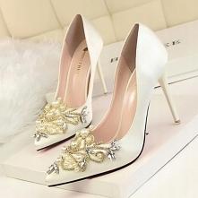 Satynowe szpilki na wysokim obcasie. Noski butów w szpic, są pięknie zdobione wszelkiego rodzaju cyrkoniami i perełkami. Idealne na ślub.
