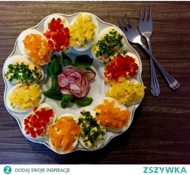 Przepis z: blogzapetytem.pl  Jajka faszerowane.  Kolorowe jajeczka faszerowane żółtym serem, szczypiorkiem oraz rzodkiewką- pięknie i smacznie zaprezentują się na świątecznym stole, ale oczywiście nie tylko. Doskonale sprawdzą się także jako weekendowe śniadanie czy przystawka na przyjęciu. Są dość łatwe i szybkie w przygotowaniu, a wyglądają bardzo efektownie.  Składniki :  6 jajek, 10 dkg żółtego sera, 3 rzodkiewki, pęczek szczypiorku, po ćwiartce papryki: żółtej, czerwonej i pomarańczowej, 2 łyżki majonezu, 1 łyżka gęstego jogurtu naturalnego, sól i pieprz.  *** Ser żółty ścieramy na tarce o drobnych oczkach a rzodkiewki, szczypiorek i papryki drobno kroimy *** *** Jajka gotujemy na twardo, studzimy, obieramy ze skorupek i przecinamy na połówki. Za pomocą łyżeczki wyciągamy żółtka ( nie uszkadzając białek) i przekładamy do miseczki. Żółtka dusimy widelcem, dodajemy majonez, jogurt, starty żółty ser, rzodkiewki i połowę szczypiorku. Dokładnie mieszamy i przyprawiamy do smaku solą oraz pieprzem *** *** Farsz przekładamy do wcześniej wydrążonych białek. Jajka dekorujemy z wierzchu drobno pokrojonymi papryczkami oraz szczypiorkiem ***