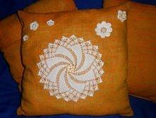Lniana poduszka z motywami robionymi na szydełku.