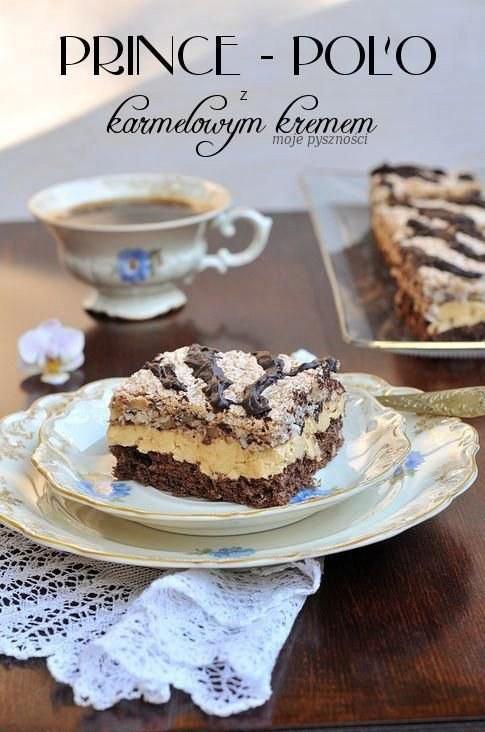 SKŁADNIKI: Biszkopt kakaowy: 5 jajek 5 łyżek (90g) cukru 4 łyżki (80g) mąki tortowej 1½ łyżki (20g) kakao 1płaska łyżeczka proszku do pieczenia Beza z Prince Polo: 6 białek 1 szklanka (190g) cukru 5 małych lub 3 duże prince polo (około 150g) 100g wiórek kokosowych 100g orzechów włoskich Krem: 150g margaryny* 150g masła 4 żółtka + 1,5 łyżki cukru** 8 łyżek rumu 1 puszka (510g) gotowej masy krówkowej 2 – 3 łyżki rumu 2 – 3 łyżki spirytusu WYKONANIE: Biszkopt kakaowy: Białka ubić z cukrem na bardzo sztywną pianę. Dodać żółtka i jeszcze ubijać, do dokładnego wymieszania. Następnie dodać przesiane przez sitko: mąkę pszenną, kakao, proszek do pieczenia i bardzo delikatnie wymieszać (najlepiej drewnianą łyżką). Wylać do formy (wyłożonej papierem do pieczenia i natłuszczonej) o wymiarach ok.40cm na 24cm. Włożyć do lekko nagrzanego piekarnika i piec około 30 minut w temperaturze 175 °C. do tzw. suchego patyczka. Beza: Białka ubić z cukrem na bardzo sztywną pianę. Do ubitej piany dodać pokrojone orzechy włoskie, kokos oraz pokruszone prince polo i bardzo delikatnie wymieszać (najlepiej drewnianą łyżką). Wylać do formy, wyłożonej papierem do pieczenia i natłuszczonej. Piec w temperaturze 175 °C około15 -20 min.( do zarumienienia ) Krem: Masło i margarynę utrzeć na puszystą masę. Żółtka ubić z cukrem na puszystą masę Do utartego tłuszczu dodawać po łyżce ubitych żółtek, cały czas ucierając. Następie dodawać porcjami masę krówkową. Na końcu dodać rum i spirytus (trzeba uważać żeby krem...