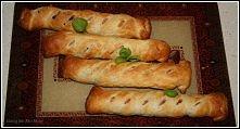 Parówki w cieście francuskim       1 arkusz ciasta francuskiego,      4 długie parówki (długość minimum 20cm),      6 suszonych pomidorów,      50g żółtego sera,      bazylia (ś...