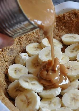 SKŁADNIKI: 6 średniej wielkości bananów śmietanka tortowa 36%, Śnieżka do zagęszczenia Toffi krówka 1 puszka czekolada gorzka (tylko do posypki) Herbatniki maślane zwykłe margaryna do pieczenia 150 gram JAK PRZYGOTOWAĆ BANOFFEE PIE: Ciasto jest warstwowe: 3 warstwy bananów, 2 warstwy toffee, 2 warstwy śmietanki.  1. Herbatniki ugnieść na miazgę, margarynę rozpuścić, połączyć herbatniki z margaryną, przełożyć do wyłożonej folią tortownicy. Ułożyć równo łyżką spód ciasta. 2. Banany pokroić w plasterki. Najlepiej 2 banany na jedną warstwę. Położyć pierwszą warstwę bananów. 3. Puszkę Toffee otworzyć. Wyłożyć na banany warstwę toffi (1/2 puszki). 4. Śmietankę ubić z śnieżką na twardą masę. Podzielić na dwie części. Wyłożyć na toffee jedną część śmietanki. 5. Powtórzyć proces: banany, toffee, śmietanka. 6. Na wierzch wyłożyć dekoracyjnie ostatnią część bananów i posypać startą czekoladą. 7. Włożyć do lodówki na minimum 2 godziny.  INFORMACJE DODATKOWE Nie krój wszystkich bananów od razu, aby nie ściemniały.Spód ciasta można przygotować również na bardziej skomplikowany sposób. Wystarczy dodać do ciastek pokruszone migdały i orzechy laskowe. Wszystko wyłożyć do tortownicy i zapiec przez 10 - 15 minut w piekarniku rozgrzanym do 180 stopni. Bez pieczenia też dobre :)  Przewidywana cena: do 17 zł Czas wykonania: 20 minut Czas oczekiwania: 2 godziny