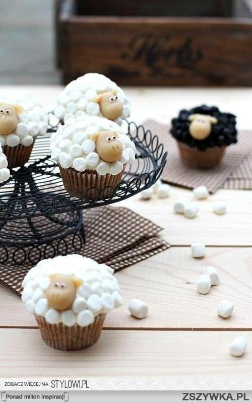Babeczki owieczki:   2 jajka  150g cukru  1 łyżeczka ekstraktu waniliowego  2 łyżki masła  150ml śmietanki kremówki 30%  175g mąki pszennej  1 łyżeczka proszku do pieczenia  1/2 łyżeczki sody  szczypta soli  100g gorzkiej czekolady, drobno posiekanej  Krem:   125g serka mascarpone  100ml śmietanki kremówki 30%  1 łyżeczka cukru waniliowego  Oraz:   marcepan ok. 150g  pianki mini-marshmallows ok. 150g  kostka gorzkiej czekolady, roztopiona  białe perełki  Przygotować babeczki. Foremkę na muffiny wyłożyć papilotkami. Jajka ubić z cukrem i wanilią na jasny, gęsty, puszysty krem. W międzyczasie roztopić masło, ubić na sztywno śmietankę kremówkę, przesiać suche składniki i wymieszać z czekoladą. Na najmniejszych obrotach miksera do ubitych jaj wlać masło, następnie dosypywać po łyżce suchych składników na zmianę z połową ubitej kremówki. Na koniec wmieszać delikatnie pozostałą śmietankę. Ciasto rozłożyć pomiędzy dołki foremki - piec 12-15 minut do suchego patyczka w 180st.C. Ostudzić na kuchennej kratce.   Przygotować krem. Serek mascarpone ubić razem z kremówką i cukrem na gęsty krem. Schować do lodówki. Przygotować owieczki. Mini-marshmallow pokroić nożyczkami na połówki. Z marcepanu ukształtować główki i uszka. Do główki przykleić uszka, oczka z perełek i narysować źrenice z czekolady, odcisnąć też nozdrza wykałaczką. Babeczki posmarować kremem. Przykleić główkę i połówki pianek