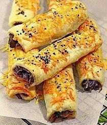 Paluchy z ciasta francuskiego z pieczarkami i cebulką Paluchy z ciasta francuskiego, nadziewane pieczarkami i czerwoną cebulką. Wierzch posypany serem żółtym i czarnuszką, która nadaje całości ciekawego smaku i aromatu. Smaczne, lekkie i szybkie. Doskonale sprawdzą się jako przekąska i danie główne, dodatek do sałaty lub czerwonego barszczu. Zapraszam :)   Składniki: opakowanie świeżego ciasta francuskiego, 250 g pieczarek 2 średnie cebule czerwone łyżeczka suszonego oregano pieprz, sól łyżka czarnuszki żółty ser,u mnie Kolumb Cebulę obrać, umyć i pokroić w półksiężyce. Zeszklić na odrobinie oleju. Pieczarki obrać, umyć i osuszyć, pokroić w plasterki. Dodać do cebuli i podsmażać kilka minut. Doprawić solą, pieprzem i oregano. Ostudzić. Ciasto francuskie pokroić na ok. 8 cm pasy, nakładać farsz i zwijać, następnie ruloniki poprzekrawać i ułożyć na blaszce wyścielonej papierem do pieczenia. Piec w piekarniku nagrzanym do 180 stopni, ok. 15-20 minut, do zrumienienia.