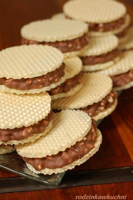 Chrupiące wafelki  Składniki:      1 paczka małych, okrągłych wafli     70 g ryżu preparowanego     250 g masła     1 i 1/2 szklanki cukru     2 czubate łyżki kakao     1/2 szklanki mleka     1-2 łyżeczki ekstraktu waniliowego     2 szklanki mleka w proszku     ew. bakalie   Wykonanie:  Masło, cukier, mleko, kakao zagotować. Dodać wanilię, przygotowane bakalie. Przestudzić, dodać mleko w proszku. Wymieszać, dodać ryż, ponownie wymieszać. Masę kłaść na wafelki, sklejać po dwa i zostawić do stężenia (najlepiej na noc)
