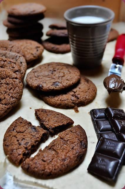 Ciasteczka z nutellą  Składniki: 190 gramów mąki pszennej 100 gramów masła 120 gramów cukru 140 gramów nutelli 50 gramów cukru trzcinowego 100 gramów czekolady gorzkiej 1 jajko 2 łyżeczki kakao 1 łyżeczka ekstraktu z wanilii ½ łyżeczki proszku do pieczenia ½ łyżeczki sody szczypta soli  Sposób przegotowania: W jednej misce wymieszać ze sobą mąkę, kakao, proszek do pieczenia, sodę oraz sól. Masło ubić razem z cukrem i cukrem trzcinowym, na jasną i puszystą masę. Następnie dodać nutellę i ekstrakt z wanilii. Zmiksować. Dodać jajko i ponownie wymieszać. Stopniowo dodać suche składniki, rozdzielając je na 3 części. Na końcu wmieszać posiekaną gorzką czekoladę. Schłodzić masę w lodówce przez minimum godzinę (opcjonalnie, jednak dzięki temu będą bardziej kruche). Łyżką nakładać kawałki ciasta, formować z nich kuleczki i układać na blaszce wyłożonej papierem do pieczenia. Następnie przy pomocy ręki lekko je rozpłaszczyć. Piec w temperaturze 150 – 180 stopni przez około 10 – 12 minut. Następnie wystudzić na kratce.