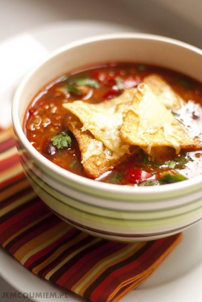 """Zupa meksykańska z mięsem mielonym Co nam będzie potrzebne: – 0,5 kg mięsa mielonego (ja użyłam wieprzowego z łopatki, oryginalnie powinna być wołowina) – 2 papryki, najlepiej różnokolorowe (dla lubiących pikantne proponuję jeszcze 1 papryczkę chilli) – 2 cebule czerwone – 3 ząbki czosnku – puszka fasoli czerwonej – puszka fasoli białej – puszka kukurydzy – puszka pomidorów – 2 łyżki przecieru pomidorowego – 4-5 szklanek rosołu, można zastąpić go kostką rosołową – papryka mielona słodka i ostra, odrobina chilli, sól, cukier, oregano – 1 łyżka soku z cytryny – pęczek natki pietruszki – olej do smażenia Przygotowanie: wszystkie warzywa myjemy i odstawiamy na sitko, żeby obeschły cebulę obieramy i kroimy w kostkę, nie musi być bardzo drobna z papryk wycinamy gniazda nasienne, czyścimy z pestek i kroimy na bardzo cienkie paseczki czosnek obieramy i siekamy drobno w dużym, głębokim garnku rozgrzewamy tłuszcz i wrzucamy pokrojoną cebulę, smażymy chwilkę, aż się zeszkli do zeszklonej cebulki dodajemy mięso i na średnim ogniu podsmażamy tak długo, aż mięso straci """"surowy"""" kolor, po czym dodajemy przyprawy (1 łyżkę słodkiej papryki, 1 łyżkę oregano, szczyptę chilli, łyżeczkę soli, 2 łyżeczki cukru, 1 łyżkę soku cytryny) do podsmażonego mięsa dodajemy pokrojoną paprykę i smażymy kilka minut, aż papryka zmięknie, po czym dodajemy pomidory (jeśli są w całości dobrze jest, przed wrzuceniem ich do garnka, rozdrobić je nieco widelcem) i posiekany czosnek chwilę smażymy wszystko razem, po czym dolewamy rosół, dodajemy przecier pomidorowy, przykrywamy garnek i na wolnym ogniu gotujemy zupę ok. 20 min. po tym czasie dodajemy fasolę i kukurydzę (pamiętajcie, żeby wypłukać je po wyjęciu z puszek) i gotujemy jeszcze ok. 10-15 minut; jeśli zupa wydaje się Wam zbyt gęsta, dolejcie do niej trochę wody w czasie, gdy zupa """"dochodzi"""" rozgrzewamy piekarnik, nie musi być bardzo gorąco, tylko na tyle, żeby rozpuścił się w nim ser; na blachę wysypujemy nachosy, posypujemy je startym serem i wkład"""