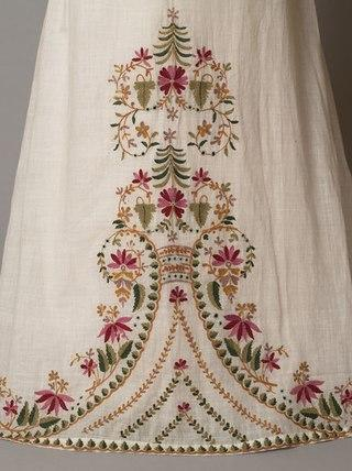 Girls dress of white muslin embroidered from the hem with a floral design in coloured wools. The dress has a high-waisted bodice, vertically-gathered puffed sleeves and a trained skirt. c. 1812-15.