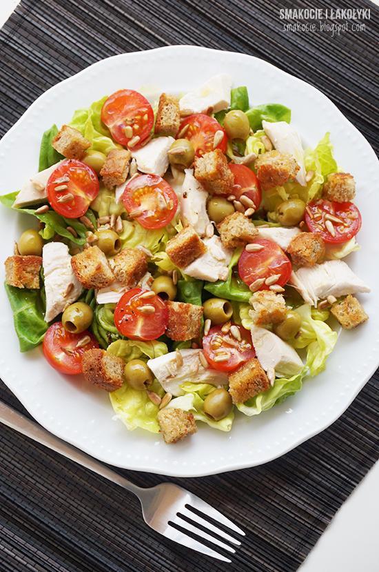 pół pieczonej/grillowanej piersi z kurczaka kromka żytniego chleba kilka liści sałaty masłowej (może być też rzymska lub inna)) oliwki zielone kilka pomidorków koktajlowych łyżka słonecznika oliwa sok z cytryny sól, pieprz