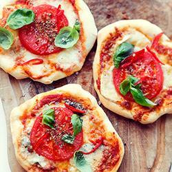 Mini pizze na przyjęcie i imprezę Składniki na 6 mniejszych pizzy: Ciasto: • 300 g mąki pszennej • 3 łyżeczki drożdży w proszku instant • 1 łyżeczka soli • 3/4 szklanki ciepłej wody (187 ml) • 2 łyżki oliwy Dodatki: • sos pomidorowy (np. z pomidorów z puszki lub ze świeżych pomidorów) • 250 g tartego sera mozzarella • świeże pomidory • dodatkowy ser: biała mozzarella w kulce, ser gorgonzola, ser kozi w roladce • papryczka chili, bazylia, suszone oregano, oliwa Przygotowanie: Do miski przesiać mąkę, dodać drożdże, sól i wymieszać. Wlać ciepłą wodę i oliwę i wymieszać łyżką. Następnie zagnieść miękkie ciasto, wyrabiać starannie przez około 15 minut aż będzie elastyczne i nie będzie się kleiło. Zostawić w misce pod przykryciem ze ściereczki do wyrośnięcia na około 45 minut. W międzyczasie przygotować dodatki oraz mocno nagrzać kamień do pizzy w piekarniku, w maksymalnej temperaturze (250-300 stopni C). Ciasto wyłożyć na stolnicę, połączyć w kulę, podzielić nożem na 6 kawałków. Każdy kawałek rozpłaszczyć w dłoniach rozciągając ciasto (a nie wałkując wałkiem!), na okrąg o średnicy około 12-15 cm. Starać się nie robić tego zbyt długo. Placki układać na desce lub łopatce do zsuwania ciasta na kamień podsypanych mąką (aby mogły się swobodnie przesuwać). Rozsmarować sos pomidorowy, posypać tartą mozzarellą, dodać pokrojone na kawałeczki sery. Dodać plasterek pomidora, posypać solą i suszonym oregano. Pomidory można też obrać i pokroić w kosteczkę. Zsuwać pizze na rozgrzany kamień (jednocześnie możemy upiec 3 pizze). Piec do lekkiego zrumienienia się brzegów pizzy, ok. 8 minut. Po upieczeniu posypać posiekaną papryczką chili, pomidora skropić oliwą, posypać bazylią.