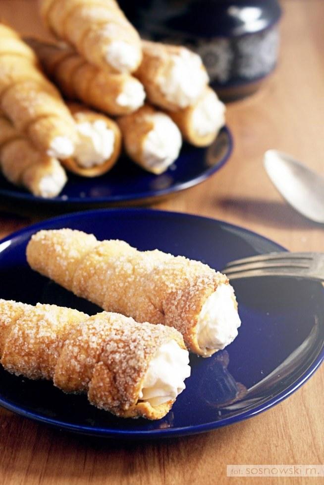 SKŁADNIKI CIASTO 160 g mąki pszennej 40 g masła 40 g kwaśnej śmietany (np. 18%) KREM 200 ml śmietany kremówki (36%) 2 łyżki cukru PRZYGOTOWANIE Krok 1 Składniki na ciasto zagnieść szybko, zwinąć w folię i schłodzić w lodówce przez ok. 30 minut. Następnie ciasto rozwałkować na bardzo cienko (ok. 1 mm grubości). Wycinać długie paski o szerokości nie więcej niż 1 cm. Krok 2 Foremki do rurek posmarować cienko masłem. Paski ciasta zawijać na foremkach zaczynając od węższej strony metalowej rurki do dołu. Nawinięte ciasto obsypać dookoła cukrem. Krok 3 Surowe ciastka ustawić pionowo na blaszce i umieścić w piekarniku. Piec w 200ºC przez ok. 20 minut do lekko złotego koloru (ja piekłem ok. 40 minut). Zdejmować z foremek jeszcze ciepłe. Krok 4 Śmietanę kremówkę ubić na sztywno, pod koniec dodać 1 łyżkę cukru. Przy pomocy szprycy nadziewać rurki kremem. Smacznego! :)