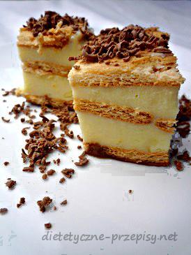 Niskokaloryczne ciasto budyniowe – 12 porcji po 100 kcal  Składniki:  150g herbatników 800 ml mleka 0,5 % tłuszczu 2 budynie w proszku bez cukru o smaku śmietankowym 80g stewia do smaku opcjonalnie dla porcji o wartości kalorycznej 125 kcal:  20g gorzkiej czekolady 30g cukru najlepiej brzozowego Przygotowanie:  Budyń przygotuj zgodnie z opisem na opakowaniu, używając mniej mleka (800 ml) oraz nie dodając cukru. Masę budyniową dosłodź stewią. Herbatniki wyłóż na dnie okrągłej formy do ciasta o średnicy 20 cm. Wylej na nie połowę budyniu. Przykryj kolejną warstwą herbatników i wylej pozostałą część budyniu. Przykryj resztą herbatników. Poczekaj, aż ciasto wystygnie i wstaw je do lodówki, żeby się schłodziło. Gotowe:)  Jeżeli chcesz przygotować wersję troszkę bardziej kaloryczną, do budyniu dodaj 2 łyżki cukru brzozowego (30 g), a wierzch ciasta posyp startą gorzką czekoladą.  PRZEPIS POCHODZI Z: dietetyczne-przepisy.net