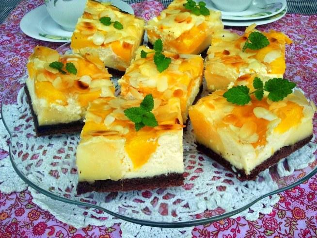 Ciasto budyniowo-serowe z nektarynką  *forma 25*34 cm Składniki: na ciasto:      1 szklanka mąki     1 łyżka cukru     1 żółtko     75 g masła     1 łyżka kwaśnej śmietany     1 łyżka kakao  na budyń:      3 opakowania budyniu waniliowego     3 szklanki mleka     5 łyżek cukru  na ser:      2 kostki sera białego półtłustego      3 jajka     4 łyżki cukru     1 białko pozostałe z ciasta     1 opakowanie budyniu waniliowego     1/2 szklanki mleka     150 g masła  dodatkowo:      10 nektarynek     garść płatków migdałowych  Składniki ciasta zagnieść, wylepić ciastem blaszkę i umieścić ją na godzinę w lodówce. Ser zmielić dwukrotnie lub nawet trzykrotnie. Na mleku ugotować budyń z cukrem. Lekko przestudzić. Masło roztopić i przestudzić. Ser zmiksować z żółtkami, cukrem, mlekiem i proszkiem budyniowym.Dodać masło. Białka ubić na sztywno i połączyć z masą serową. Nektarynki obrać ze skórki i pokroić na cząstki. Na ciasto wykładać kupkami budyń i ser. Na wierzchu ułożyć nektarynki i posypać płatkami migdałów. Piec w 180*C około godziny. Studzić jak sernik najlepiej całą noc.