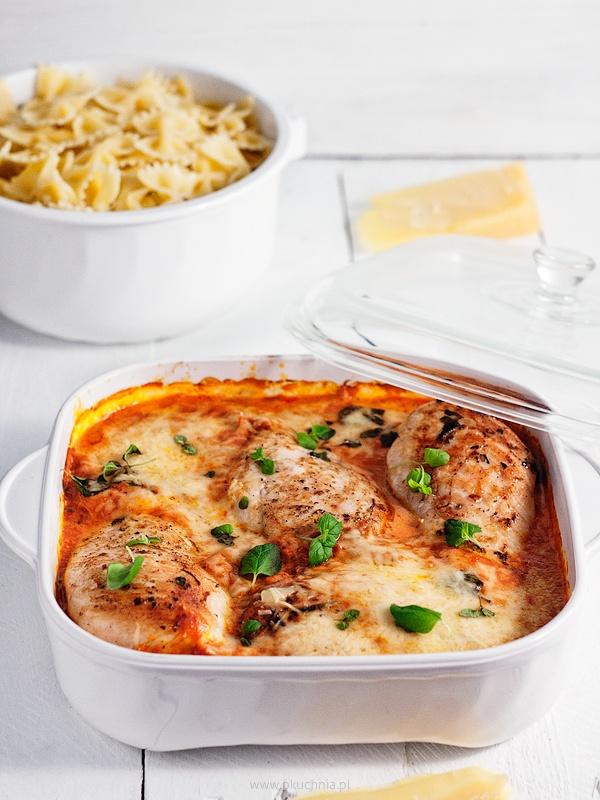SKŁADNIKI ( 3 – 6 osób): 6 filetów pojedynczych filetów z kurczaka, czyli 3 podwójne 1 puszka krojonych pomidorów (w sezonie świeże) 1 cebula 2 ząbki czosnku 50 g parmezanu (lub innego b. twardego dojrzewającego sera – grana padano, pecorino, mazuriano) 100 ml słodkiej śmietanki 30% 2 łyżeczki suszonego oregano garść świeżego oregano 1/2 łyżeczki chili pieprz, sól i cukier oliwa WYKONANIE: Filety myjemy i osuszamy. Dwie łyżki oliwy mieszamy z solą, chili i łyżeczką suszonego oregano i marynatą nacieramy mięso. Pozostawiamy je na godzinę na blacie. Cebulę i czosnek drobno siekamy i smażymy na oliwie do zeszklenia. Dodajemy pomidory, trochę wody (około 50 – 100 ml) , doprawiamy suszonym oregano (1 łyżeczkę), pieprzem i cukrem (jeśli pomidory są zbyt kwaśne). Dusimy na średnim ogniu przez około 10 minut. Parmezan ścieramy na tarce o małych oczkach. Do sosu dodajemy śmietanę, połowę sera i w razie potrzeby doprawiamy jeszcze solą. Na patelni rozgrzewamy oliwę i podsmażamy filety z obu stron na dużym ogniu, tylko do zrumienienia. Ważne jest aby nie przesmażyć filetów, gdyż będą potem suche. Przekładamy je do naczynia żaroodpornego, polewamy sosem i posypujemy resztą sera. Wstawiamy do piekarnika nagrzanego do 180 st. C i zapiekamy około 30 minut bez przykrycia. Podajemy z makaronem, posypane świeżym oregano.