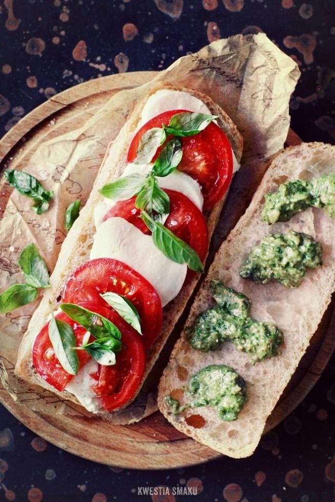 """Ciabatta caprese z zielonym pesto Przygotowywana na ciepło w zgrzewarce lub opiekaczu, z ciągnącym się serem i chrupiącą bułeczką  Składniki, 2 porcje:  • 2 ciabatty (domowe ciabatty: przepis 1 lub przepis 2) • oliwa z oliwek z pierwszego tłoczenia • 1 pomidor • 1 kulka mozzarelli (125 g) • kilka liści bazylii  Pesto: (około 1/2 szklanki):  • bazylia lub rukola, 1 szklanka liści • 1/3 ząbka czosnku • 25 g pestek dyni lub orzeszków pinii • 1 łyżka tartego Parmezanu lub Grana Padano lub Pecorino lub Manchego • 50 ml oliwy z oliwek z pierwszego tłoczenia • sól morska i świeżo zmielony czarny pieprz do smaku  Przygotowanie:  Pesto: wszystkie składniki (oprócz kilku listków bazylii) utrzeć w moździerzu lub zmiksować ręcznym blenderem (mają pozostać małe drobinki składników). Doprawić solą morską i pieprzem. Ciabatty przekroić w poprzek na 2 części. Na jednej połówce ułożyć """"na zakładkę"""" plasterki pomidorów i mozzarelli, doprawić solą i pieprzem, posypać listkami bazylii. Drugą połówkę posmarować pesto (resztę wstawić do lodówki). Złożyć na pół i włożyć do zgrzewarki lub opiekacza na około 2 minuty, do czasu aż ser się roztopi a pieczywo będzie chrupiące z zewnątrz."""