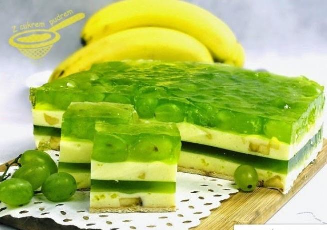 """15 - 20 sztuk herbatników typu petitki masa bananowa I: 500 gramów gęstego jogurtu bananowego (polecam FruVita z Biedronki) 2 średnie banany 2 galaretki cytrynowe 200 ml gorącej wody galaretka zielona: 2 galaretki agrestowe masa bananowa II: 500 gramów gęstego jogurtu bananowego 2 średnie banany 2 galaretki cytrynowe 200 ml gorącej wody wierzch: 600 - 700 gramów zielonych winogron 2 galaretki agrestowe Jogurty wyjmujemy z lodówki około 1 godziny przed przystąpieniem do pracy, żeby nie były bardzo zimne. Polecam ten jogurt, tani, gęsty i bardzo smaczny. Spód blaszki 25x25 cm lub 25x30 cm wykładamy herbatnikami. Galaretki cytrynowe rozprowadzamy w 200 ml gorącej wody, schładzamy do temperatury pokojowej. Następnie miksujemy z jogurtem, wrzucamy banany pokrojone w kosteczkę, delikatnie mieszamy. Masę wkładamy do lodówki, kiedy będzie miała konsystencję gęstej śmietany wylewamy ją na herbatniki, wstawiamy do lodówki do zgęstnienia. Od razu zabieramy się za galaretkę. Obie agrestowe rozprowadzamy w 800 ml gorącej wody, schładzamy, kiedy zaczną tężeć wylewamy je na zastygniętą masę jogurtową. Wkładamy do lodówki do zgęstnienia. Potem przygotowujemy drugą warstwę jogurtowo - bananową, tak jak w przypadku pierwszej. Kiedy druga warstwa bananowa jest już stężała, układamy na niej winogrona (oczywiście wcześniej porządnie umyte i osuszone). Ostatnie dwie galaretki agrestowe rozpuszczamy w 900 ml wrzątku, schładzamy, kiedy zaczną tężeć, wykładamy je na winogrona. UWAGA: Zalewanie winogron możemy przeprowadzić również w inny sposób (ja tak właśnie zrobiłam), najpierw zalałam owoce odrobiną całkiem płynnej galaretki, aby winogrona się """"przykleiły"""", a potem dodałam tężejącą resztę, ale (!) w przypadku tej metody musimy mieć pewność, że foremka jest szczelna. Ciasto schładzamy w lodówce optymalnie przez kilkanaście godzin."""