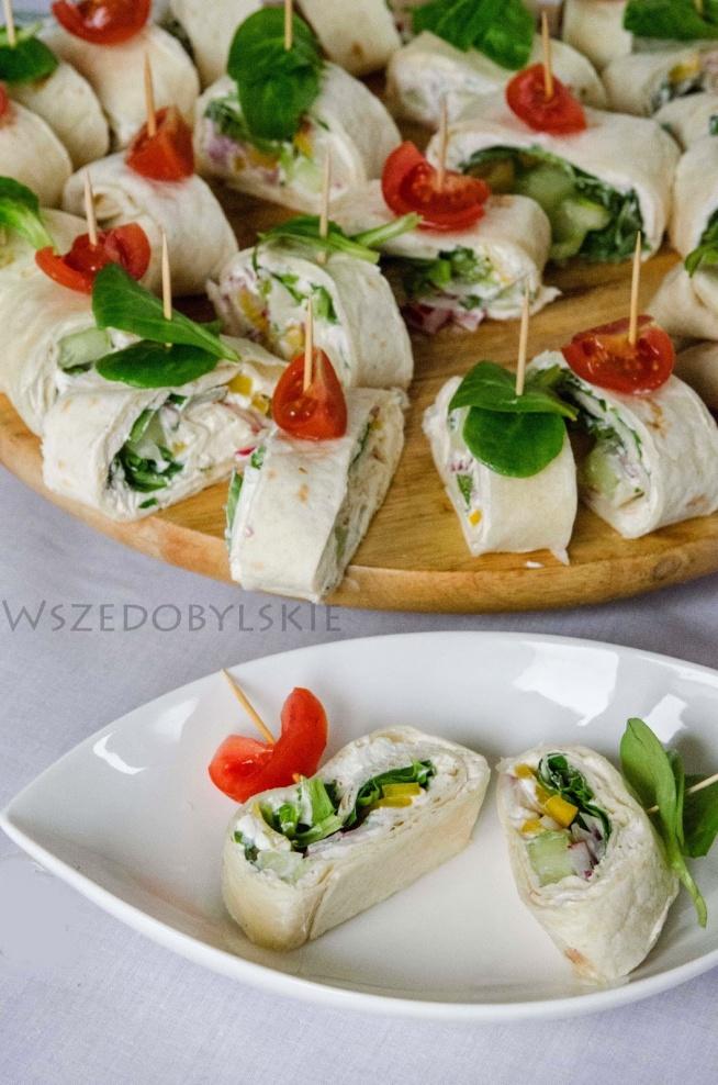 Wiosenne roladki :) Składniki: 5 placków tortilli, 1 opakowanie serka kremowego, pęczek dymki, kilka liści sałaty 1 papryka żółta kilka rzodkiewek 2 zielone ogórki sól, pieprz, garść liści bazylii lub mięty Przygotowanie: Serek mieszamy z solą, pieprzem i posiekanymi ziołami, a następnie rozsmarowujemy go na tortillach. Na serku układamy liście sałaty oraz pokrojone w paski ogórki, paprykę, rzodkiewki oraz posiekaną dymkę. Zwijamy w rulony i kroimy na 2 cm roladki. ozdabiamy pomidorkami koktajlowymi listami bazylii lub roszponki. Gotowe.