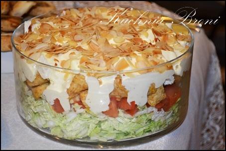 """Sałatka warstwowa z serem feta Składniki:  1/2 kapusty pekińskiej  5 pomidorów  500g piersi z kurczaka  Ser feta """"Fawita"""" 270g z """"Mlekowita""""  10dkg Płatków migdałów  Sos czosnkowy:  1 mały majonez  1 mała śmietana 18%  2 ząbki czosnku  sól,pieprz  Mięso z kurczaka pokroić w drobną kostkę, usmażyć na patelni z dodatkiem przyprawy do drobiu, odsączyć na papierowym ręczniku i odstawić do wystygnięcia. Kapustę pekińską pokroić w paseczki,pomidory w drobną kostkę, a ser feta  w kostkę 1cm na 1cm. Migdały zrumienić na suchej  patelni (bez dodatku tłuszczu).  Przygotować sos czosnkowy: Wszystkie składniki sosu połączyć ze sobą i doprawić.  Układać kolejno w szklanym naczyniu:  kapusta  pomidory  pierś z kurczaka  ser feta  polać wszystko przygotowanym sosem czosnkowym i posypać uprażonymi migdałami.Odstawić na 2-3 godziny."""