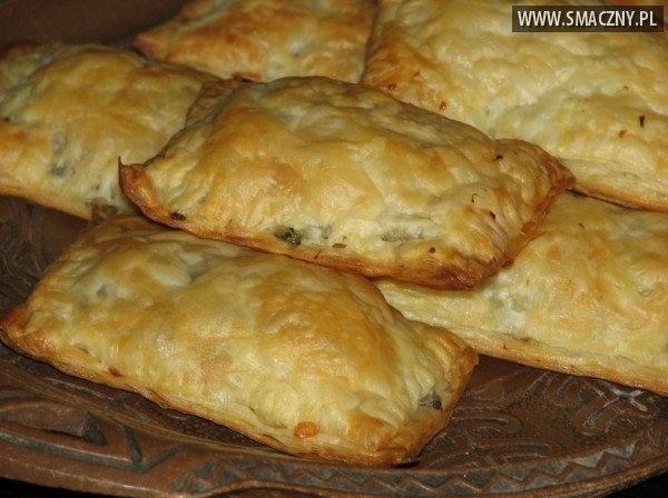 Pakieciki z brokułem i pieczarkami w cieście francuskim Składniki: Farsz: 1 brokuł (50 dag) 50 dag pieczarek 10 dag cebuli (1 średnia) 1 łyżka masła sól pieprz przyprawa gyros 10 dag żółtego sera 2 ząbki czosnku majeranek Dodatkowo: 2 opakowania ciasta francuskiego (2 x 275 g) Sposób wykonania: Brokuł opłukać, osuszyć i podzielić na różyczki. Wrzucić do wrzącej osolonej wody i od momentu zagotowania się wody, gotować 5 minut. Następnie odcedzić, ostudzić i pokroić. Pieczarki, opłukać i zatrzeć lub pokroić na plasterki. Cebulę obrać i pokroić w kostkę. Razem z pieczarkami przełożyć na patelnie. Dodać masło, szczyptę soli, pieprzu i przyprawy gyros. Razem wymieszać, rumienić i ostudzić. Żółty ser zetrzeć na tarce o dużych oczkach. Czosnek obrać i zmiażdżyć. Do miski przełożyć brokuł, pieczarki i żółty ser. Dodać czosnek, majeranek i ewentualnie przyprawić do smaku solą i pieprzem. Wszystko razem wymieszać. Ciasto francuskie rozłożyć i pokroić na około 16 części np. na prostokąty (o wymiarach około 7 na 10 cm). Drugie ciasto francuskie też pokroić na 16 części. Na jeden kawałek ciasta, na środek kłaść łyżką farsz i przykryć drugim kawałkiem ciasta. Brzegi skleić palcami i dodatkowo docisnąć widelcem. Do prostokątnej formy o wymiarach 25 na 36 cm włożyć papier, na którym było ciasto francuskie lub zwykły papier do pieczenia. Na nim ułożyć gotowe pakieciki. Całość włożyć do nagrzanego piekarnika i piec przez około 25 minut w temperaturze 180 °C. Podawać na ciepło z czerwonym barszczem do picia. Z podanych składników wyjdzie 16 pakiecików z brokułem i pieczarkami. Smacznego.