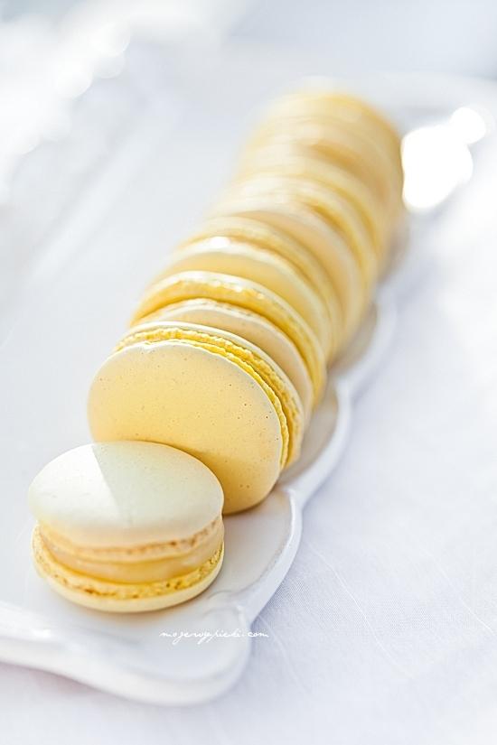 Makaroniki cytrynowe Składniki na około 30 ciastek      150 g zmielonych migdałów     150 g cukru pudru     120 g białek (podzielone na 60 g + 60 g), w temperaturze pokojowej     185 g cukru (podzielone na 150 g + 35 g)     50 ml wody     barwnik w paście/żelu - użyłam barwnika Wilton w kubeczku (kolor lemon yellow)  Migdały i cukier puder umieścić w malakserze. Zmiksować do połączenia, przez około 2 minuty. Przesiać przez bardzo drobne sitko do większego naczynia usuwając wszelkie większe kawałki migdałów (w to miejsce dosypać nowych, drobniejszych, zazwyczaj jest to około 1 łyżeczki). Dodać 60 g białek, dokładnie wymieszać. Dodać dowolną ilość barwnika, wymieszać (uwaga: barwa powinna być intensywna, białka dodawane później rozrzedzą kolor).  W misie miksera umieścić dodatkowe 60 g białek (misa powinna być sucha, bez śladów tłuszczu, białka idealnie oddzielone od żółtek). Obok w małym kubeczku przygotować 35 g cukru.  W małym garnuszku umieścić 150 g cukru i 50 ml wody. Wymieszać, zagotować. W garnuszku umieścić termometr cukierniczy i gotować na średniej mocy palnika (ważne: nie mieszając ani razu!) do osiągnięcia na nim temperatury 118ºC (245ºF).   W międzyczasie, gdy syrop dochodzi do temperatury 100ºC (210ºF) zacząć ubijać białka. Białka ubijać jak na bezy - do sztywności, pod koniec miksowania dosypując cukier, łyżeczka po łyżeczce, cały czas miksując. Gdy syrop osiągnie wymaganą temperaturę natychmiast ściągnąć go z palnika i powoli, cienką strużką wlewać syrop cukrowy do ubijanych białek (ubijamy na razie na małych obrotach - tylko podczas wlewania syropu cukrowego, by nie znalazł się na ściankach misy, ale w samych białkach, następnie obroty zwiększamy do maksymalnych), nie zaprzestając miksowania. Miksowanie kontynuować przez 5 - 8 minut do wystudzenia bezy.   Gotową włoską bezę dodawać do przygotowanej masy migdałowej, w trzech turach, dokładnie mieszając. Masa będzie robiła się rzadsza z każdym zamieszaniem, a w rezultacie powinna swobodnie opadać ze sz