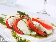 Ser mozzarella oraz umyte pomidory pokroić w plastry Plasterki mozarelli i pomidorów ułożyć na przemian na talerzu Bazylię zblendować z oliwą z oliwek i przeciśniętym przez pras...