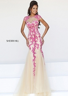 This stunning evening gown features a sheer top over sweetheart bodice with e...