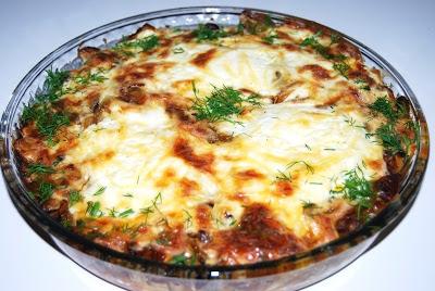 Jajka zapiekane z pieczarkami  6 średnich ugotowanych ziemniaków w mundurkach. 3 jajka 400 g pieczarek 1 cebula 250 ml śmietany 100 g żóltego sera 2 łyżki posiekanego koperku 1 łyżka masła klarowanego sól pieprz papryka ostra papryka słodka  Wykonanie: Ugotowane ziemniaki obrać i pokroić w plastry. Pieczarki pokroić w plasterki. Na patelni rozgrzać masło i lekko zeszklić cebulę pokrojoną w piórka po czym dodać pieczarki . Smażyć do odparowania wody. Doprawić solą i pieprzem. Naczynie do zapiekania wysmarować masłem i na dno ułożyć plastry ziemniaków, a następnie pieczarki. Zrobić w pieczarkach trzy dołki i w każdy wbić jajko. Śmietanę wymieszać ze startym żółtym serem, solą, pieprzem, papryką i zalać całość. Piec w 180 stopniach około 15 minut, aż śmietana z serem się przyrumieni. Przed podaniem posypać koperkiem.