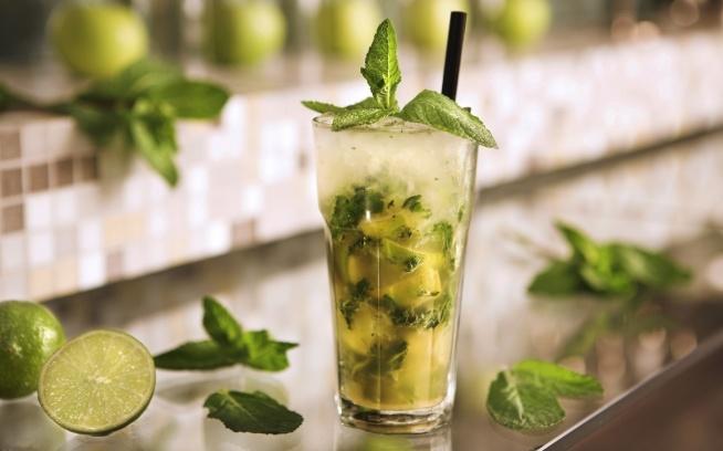 MOJITO  Składniki: 3 łyżeczki brązowego cukru 1/2 limonki pęczek mięty 50 ml białego rumu (np. Bacardi) 150-200 ml wody gazowanej lub napoju Schweppes czy Sprite kruszony lód (ewentualnie kostki lodu)  Przygotowanie: Przekrój limonkę na 3 części.  Nasyp do szklanki 3 łyżeczki brązowego cukru. Wyciśnij do szklanki sok z limonek a następnie włóż do środka również skórki. Dodaj liście mięty. Wszystko dokładnie wymieszaj. Rozgnieć liście mięty i skórki limonki moździerzem. Nałóż do szklanki lodu (około 1/3 szklanki). Dodaj rum. Szklankę wypełnij napojem lub wodą gazowaną. Drinka udekoruj plasterkiem limonki oraz listkiem mięty.
