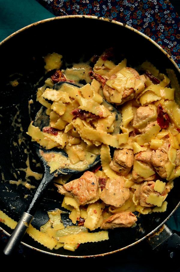 Kurczak z suszonymi pomidorami i makaronem w kremowym sosie z mozzarelli  3- 4 porcje  składniki: - 500 g piersi z kurczaka - 240 g suchego makaronu wstążki - 300 g śmietanki kremówki 30% lub 12%- słodkiej! - 1 szklanka startej mozzarelli- ok 1.5 kulki - 125 ml wody z gotowania makaronu - 5 suszonych pomidorów w oleju - 1/2 łyżeczki bazylii suszonej - 1/2 łyżeczki czerwonej pasty curry - 1 ząbek czosnku - sól, pieprz, papryka wędzona mielona ostra  Wszystkie składniki powinny być w temperaturze pokojowej Pierś dokładnie obrać z wszelkich błon, następnie pokroić w większą kostkę i doprawić solą, pieprzem oraz papryką wędzoną. Na patelni rozgrzać ok 2 łyżki oliwy, po czym wrzucić kurczaka i smażyć na dosyć dużym ogniu do zrumienienia, odstawić na talerz. Kurczak powinien być prawie usmażony. Do tej samej patelni wrzucić pokrojone w większe kawałki suszone pomidory oraz drobno posiekany czosnek, wszystko smażyć paręnaście sekund. Do patelni dodać kremówkę, pastę curry oraz bazylię, zagotować i dorzucić mozzarellę. Mieszać, czekając, aż się rozpuści.* W międzyczasie ugotować makaron al dente. Podczas odsączana makaronu zachować 125 ml wody po gotowaniu. Kiedy sos będzie gęstnieć dodać kurczaka, następnie makaron. Wszystko dobrze wymieszać ze sobą, przyprawiając solą i pieprzem. Jeśli sos będzie za gęsty dolewać stopniowo wodę z makaronu i rozrzedzić sos. Podawać natychmiast. Smacznego!  * jeśli mozzarella nie będzie chciała się do końca rozpuścić, dodajcie makaron oraz wodę po makaronie, wszystko trochę pogotować -sos w tym momencie powinien zrobić się absolutnie kremowy