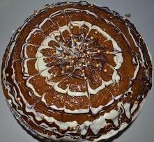 Tort korzenny z waniliowym kremem mascarpone, bitą śmietaną, kajmakiem i polewą z białej i deserowej czekolady.
