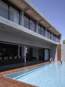 Surowa forma bryły budynku wznosząca się nad sąsiadującym bezpośrednio nowoczesnym basenem bez krawędzi w luksusowej rezydencji Hezelia Home w Izraelu. Wykorzystanie nowoczesnyc...