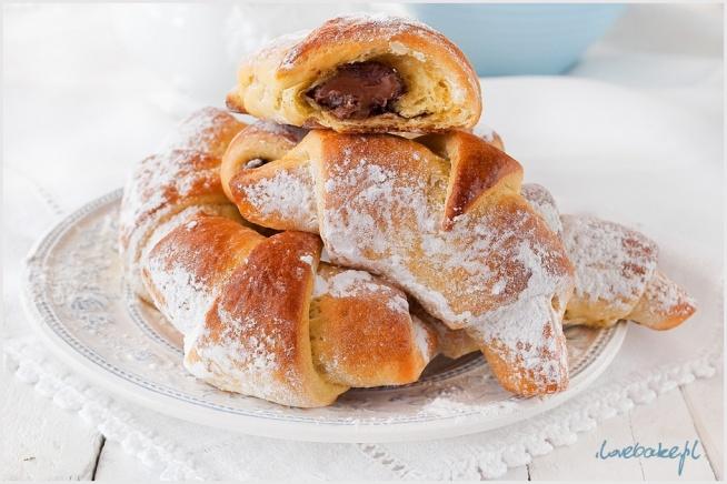 ROGALIKI DROŻDŻOWE NA JOGURCIE Z KREMEM CZEKOLADOWYM   SKŁADNIKI  NA CIASTO: ILOŚĆ: ok. 2 blaszki rogalików 500g mąki tortowej 200ml jogurtu greckiego, temp. pokojowa 50g drożdży świeżych lub 25g suchych 2 żółtka 2 łyżeczki cukru 2 łyżeczki cukru waniliowego 100g masła lub margaryny, temp. pokojowa szczypta soli  NA KREM CZEKOLADOWY: 100-150g mlecznej czekolady (ew. nutella)  DODATKOWO: 1 żółtko + 1 łyżka mleka cukier puder do oprószenia   Mąkę przesiewamy, dodajemy żółtka, cukry, sól oraz rozdrobnione w jogurcie drożdże świeże lub suche. Chwilę mieszamy, następnie dodajemy masło i wyrabiamy (ok. 5 min). Ciasto powinno być gładkie i elastyczne. Dzielimy je na dwie części, owijamy folią spożywczą i wkładamy na 2-3 godz do lodówki. Stolnicę lekko oprószamy mąką i rozwałkowujemy na kształt koła. Dzielimy na ósemki i nakładamy na każdy kawałek łyżeczkę posiekanej czekolady lub nutelli. Zawijamy od szerszej ku węższej części. Rogaliki układamy na blaszce wyłożonej papierem do pieczenia. Dokładnie tak samo postępujemy z drugą kulką. Rogaliki przykrywamy ściereczką lub folią spożywczą i zostawiamy na 20 min do napuszenia. Przed pieczeniem smarujemy żółtkiem wymieszanym z mlekiem. Pieczemy w temp. 180 C przez około 20 min, aż do zarumienienia. Oprószamy cukrem pudrem.