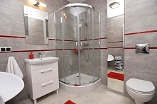 Wykończona łazienka, wykonana w ramach projektowania oraz aranżacji wnętrza pod klucz dla apartamentowca w Darłówku. Wnętrze łazienki utrzymane jest w jasnej kolorystyce z czerw...